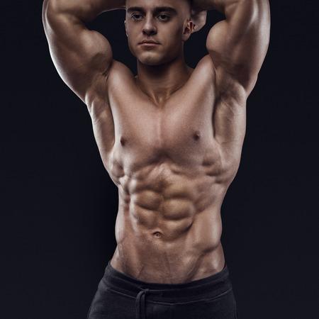 abdominal fitness: Modelo masculino atractivo fisicoculturista joven descamisado que presenta sobre fondo negro. Estudio disparó sobre fondo negro.
