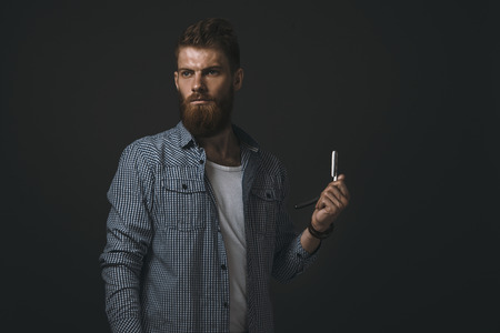 straight razor: Brutal bearded man with straight razor