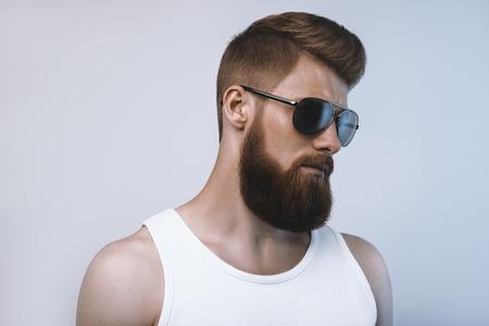 ひげを生やした男はサングラスをかけています。白い背景で撮影スタジオ