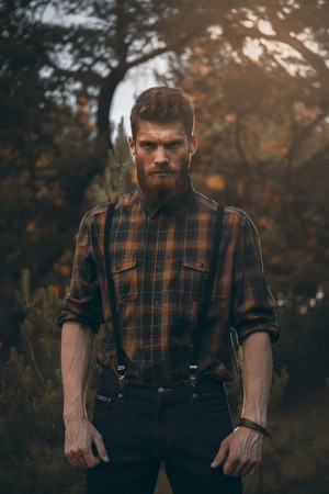 Brutal bearded man standing alone in forest outdoor with sunset nature on background