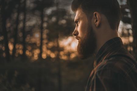 Brutal bebaarde man met vertrouwen tegemoet. Alleen te staan in het bos buiten met zonsondergang natuur op de achtergrond Stockfoto