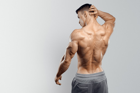 male chest: Shirtless athletic man turned back on white background.