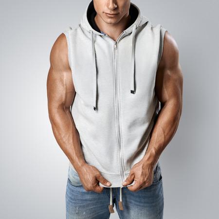 Close up photo of attractive fitness man wearing blank light gray sleeveless hoodie. Studio shot on white background. Фото со стока