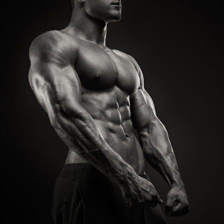 male body: Handsome power athletic man with dumbbell confidently looking forward. Strong bodybuilder with six pack, perfect abs, shoulders, biceps, triceps and chest