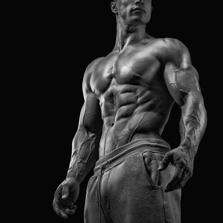 Sterke en knappe jonge man met spieren en biceps. Close-up van een elektriciteitscentrale fitness man. Zwart-wit foto Stockfoto