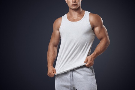 strong boy: Close up photo of attractive bodybuilder wearing blank white sleeveless t-shirt, vest Stock Photo