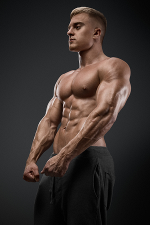 the athlete: Handsome power athletic man with dumbbell confidently looking forward. Strong bodybuilder with six pack, perfect abs, shoulders, biceps, triceps and chest