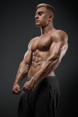 deportista: Poder guapo hombre atlético con pesas con seguridad mirando hacia adelante. Culturista fuerte con paquete de seis, perfectos abdominales, hombros, bíceps, tríceps y pecho Foto de archivo