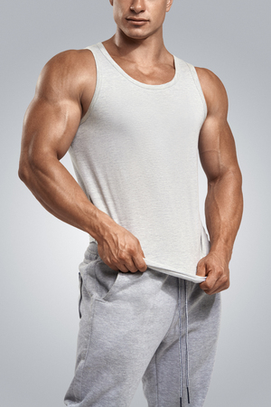 tank: Young athlete wearing blank white vest, sleeveless t-shirt. Studio shot on white background.
