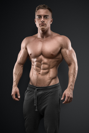 Handsome power athletic man posing on black background. Strong bodybuilder with six pack, perfect abs, shoulders, biceps, triceps and chest Фото со стока