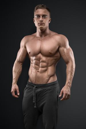 Knap macht atletische man die zich voordeed op zwarte achtergrond. Sterke bodybuilder met zes pack, perfect abs, schouders, biceps, triceps en borst