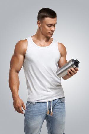 Muscular culturista masculino de la aptitud proteína que sostiene la botella batido listo para beber. Estudio disparó sobre fondo blanco. Foto de archivo - 44585840