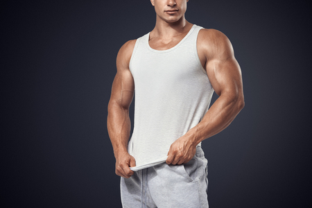 gym clothes: Close up photo of attractive bodybuilder wearing blank white sleeveless t-shirt, vest Stock Photo
