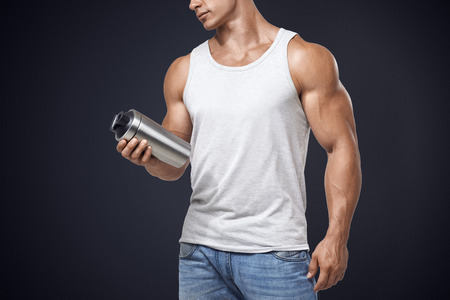 protein food: Muscular fitness male bodybuilder holding protein shake bottle ready for drinking. Studio shot on dark background. Stock Photo