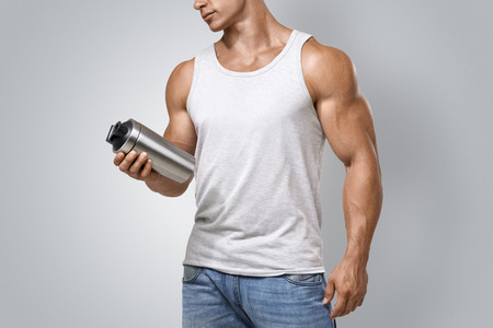 Muscular fitness male bodybuilder holding protein shake bottle ready for drinking. Studio shot on white background.