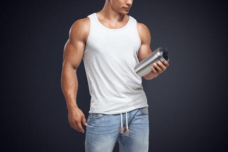 Muscular fitness male bodybuilder holding protein shake bottle ready for drinking. Sports nutrition. Studio shot on dark background. 版權商用圖片