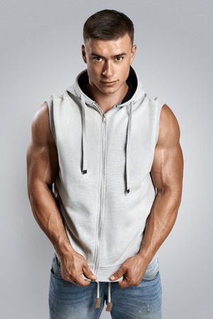 sleeveless hoodie: Handsome bodybuilder wearing blank light gray sleeveless hoodie isolated on white background.