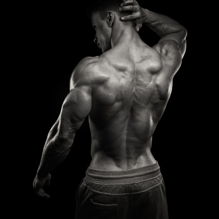 human chest: Handsome power athletic man turned back. Isolated over black background. Strong bodybuilder with shoulders, biceps, triceps and chest