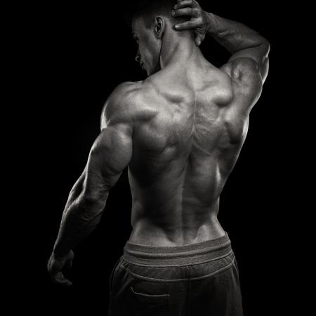 espalda: Poder guapo hombre atlético volvió. Aislado sobre fondo negro. Culturista fuerte con los hombros, bíceps, tríceps y pecho