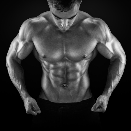 Strong athletic man fitness model torso showing six pack abs, perfect abs, shoulders, biceps, triceps and chest. Black and white photo
