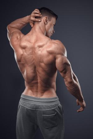 shirtless: Poder guapo hombre atlético volvió. Aislado sobre fondo negro. Culturista fuerte con los hombros, bíceps, tríceps y pecho