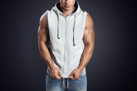 sleeveless hoodie: Close up photo of attractive fitness man wearing blank light gray sleeveless hoodie. Studio shot on dark background.