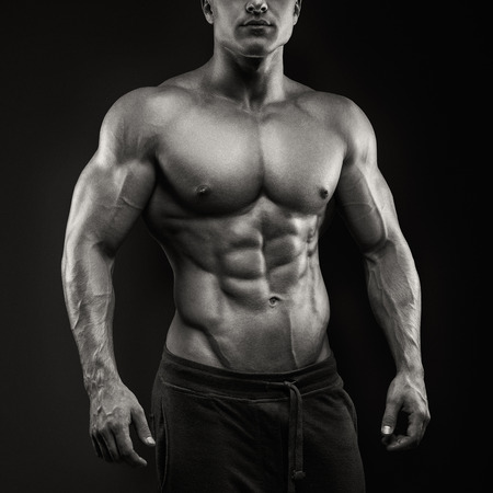 musculoso: Apuesto hombre atlético de energía que presenta en fondo negro. Culturista fuerte con paquete de seis, perfectos abdominales, hombros, bíceps, tríceps y pecho