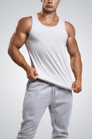 Studio shot of a handsome young fitness man wearing white blank tank top isolated on white background Stock Photo