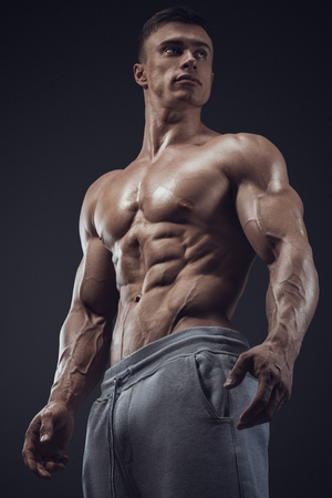 hombre sin camisa: Primer plano de un hombre de fitness poder. Hombre joven fuerte y guapo, con los músculos y los bíceps. Estudio de fotografía en fondo negro.