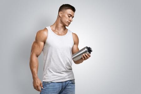 Musculaire fitheid mannelijke bodybuilder die proteïne shake fles klaar om te drinken. Studio opname op een witte achtergrond.