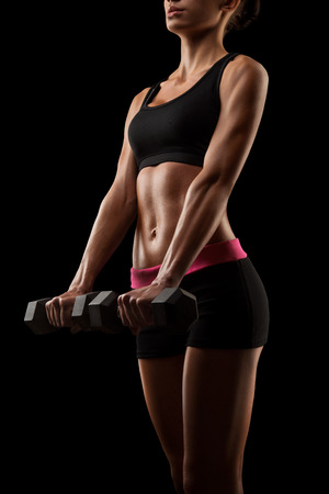 Fitness sporty woman in training pumping up muscles with dumbbells. Young sports sexy fitness woman body with dumbbells posing on black background, isolated.