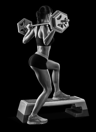 athletic body: Strong young woman with beautiful athletic body doing exercises with barbell. Black and white photo