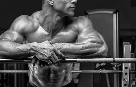 men body: Close up of handsome bodybuilder guy prepare to do exercises with barbell in a gym. Black and white photo.