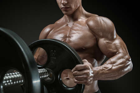 male body: Closeup photo of handsome bodybuilder guy prepare to do exercises with barbell in a gym, keep barbell plate in hands