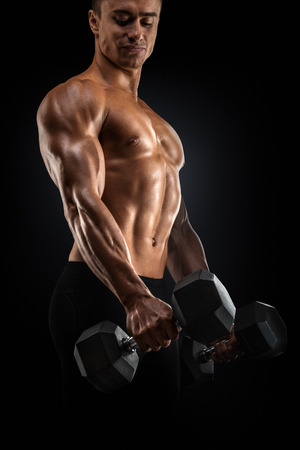 six pack: Handsome power athletic man in training pumping up muscles with dumbbell. Strong bodybuilder with six pack, perfect abs, shoulders, biceps, triceps and chest