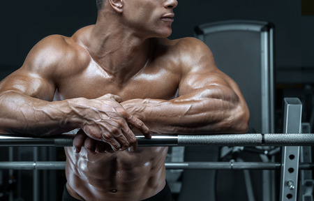 Close up photo of power bodybuilder guy prepare to do exercises with barbell in a gym Stock Photo