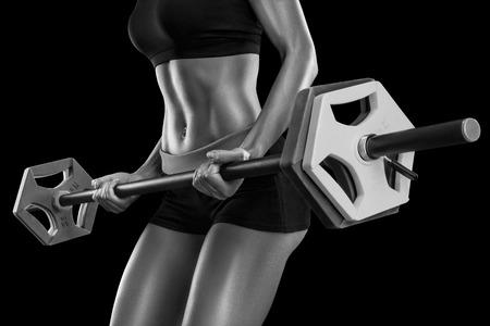 mujer celulitis: Hermosa mujer joven ejercicios con mancuerna aislado sobre fondo negro. foto en blanco y negro. Foto de archivo