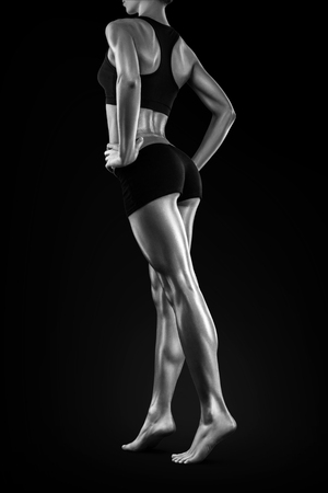 woman black background: Perfect shaped woman walking on black background. Torning back and perfect fit long woman legs showing. Black and white photo.