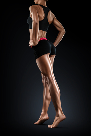 perfect fit: Perfect shaped woman walking on black background. Turning back and perfect fit long woman legs showing.