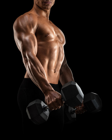 six pack: Close-up of handsome power athletic mans hand in training pumping up muscles with dumbbell. Strong bodybuilder with six pack, perfect abs, shoulders, biceps, triceps and chest