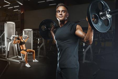 Jong en fit paar in de sportschool doen training. Groep vrouwen en mannen bodybuilders training op speciale sport-apparatuur in de sportschool. Sport, bodybuilding, lifestyle en mensen concept.