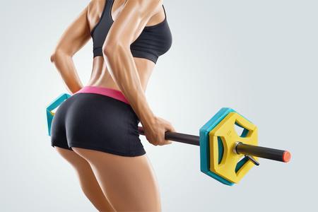 Close-up portret van mooie vrouw fitness workout met barbell op gymnasium. Perfecte pasvorm atletische jonge vrouw met een six pack, perfect abs, schouders, biceps, triceps en borst. Deadlift halters workout.