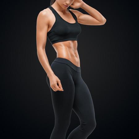 Fitness sportliche Frau, die ihre gut ausgebildeten Körper. Starke Bauchmuskeln zeigen.