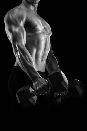 six pack: Handsome power athletic man in training pumping up muscles with dumbbell. Strong bodybuilder with six pack, perfect abs, shoulders, biceps, triceps and chest. Black and white photo.