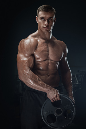 hombres sin camisa: Hombre joven hermoso que hace ejercicios atléticos confiado con placa de barra. musculoso cuerpo sobre fondo oscuro. los deportes de fitness. Cuidado de la salud, cuidado del cuerpo y el concepto físico. Foto de archivo