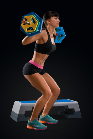 perfect fit: Portrait of beautiful fitness woman workout with barbell at gym. Perfect fit athletic young woman with six pack, perfect abs, shoulders, biceps, triceps and chest. Deadlift barbells workout.