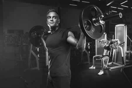 Young and fit couple in the gym doing workout. Group of women and men bodybuilders training on special sport equipment in the gym. Sport, bodybuilding, lifestyle and people concept. Black and white photo. Stock Photo
