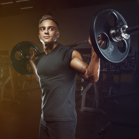 Confident muscular man training squats with barbells over head. Closeup portrait of professional bodybuilder workout with barbell at gym. Stock Photo