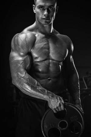 fitness hombres: Hombre joven hermoso que hace ejercicios atléticos confiado con placa de barra. musculoso cuerpo sobre fondo oscuro. los deportes de fitness. Cuidado de la salud, cuidado del cuerpo y el concepto físico. Foto de archivo