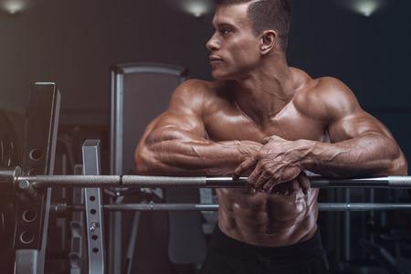 Aantrekkelijke gespierde bodybuilder man voor te bereiden om oefeningen met barbell doen in een sportschool